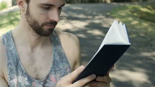 Handsome man reading interesting book and smiling to the camera, steadycam shot