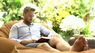 Handsome man reading interesting book while sitting on bean bag chair