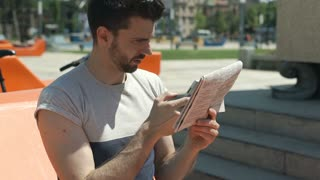 Handsome man reading newspaper and checking news in the internet, steadycam shot