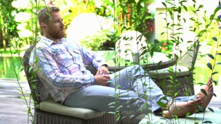 Handsome man relaxing in exotic garden and smiling to the camera