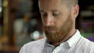 Handsome man sitting in restaurant and looks absorbed, close up, steadycam shot