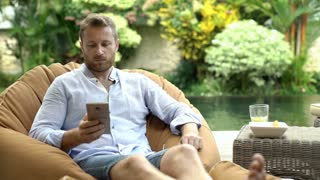 Handsome man sitting on bean bag chair and chatting on cellphone