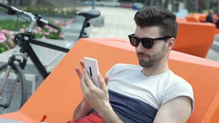 Handsome man sitting on the orange seat and browsing internet on smartphone, ste