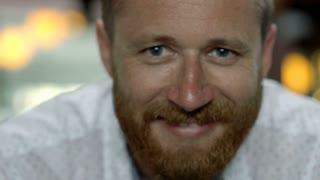 Handsome man smiling to the camera in restaurant, close up, steadycam shot