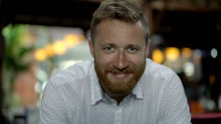 Handsome man smiling to the camera in restaurant, steadycam shot