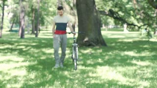 Handsome man walking with his bicycle in the park and looks relaxed, steadycam s