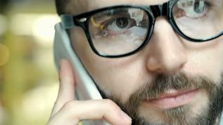 Handsome man with beard wearing glasses and talking on cellphone, close up, stea