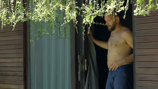 Handsome man with naked torso going outside and looks relaxed, steadycam shot, s
