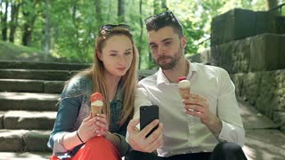 Happy couple eating ice creams and doing photos on smartphone, steadycam shot