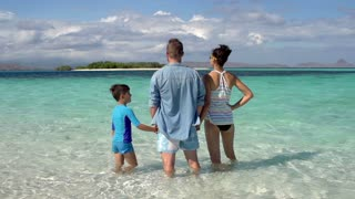 Happy family standing in the sea and waving to the camera, steadycam shot, slow