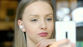 Happy girl listening music on earphones and browsing internet on smartphone, ste