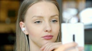 Happy girl listening music on earphones and browsing internet on smartphone, ste