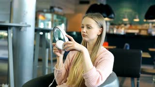 Happy girl puts on headphones and plays music on smartphone