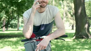 Happy man leaning on his bike and chatting on cellphone in the park, steadycam s