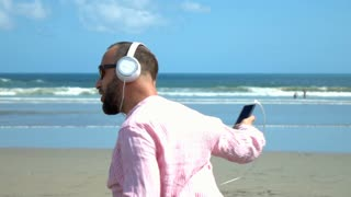 Happy man listening music and dancing on the beach, slow motion shot at 240fps,