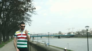 Happy man walking on boulevards and having a videocall on smartphone, steadycam