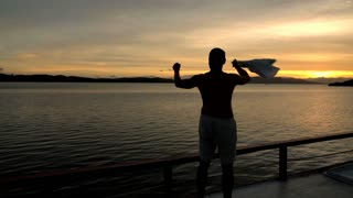 Happy man waving with a shirt at the evening on the boat, slow motion shot at 24