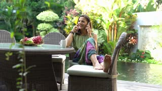 Happy woman chatting on cellphone and drinking coffee in the garden, steadycam s