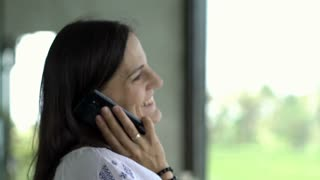 Happy woman chatting on cellphone and receives good news, close up, steadycam sh