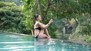 Happy woman sitting on the edge of swimming pool and having a videocall on smart