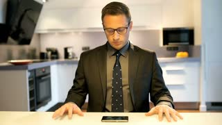 Impatient businessman watching something on smartphone and having a success