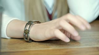 Irritated girl tapping on the table with her fingernails while waiting for somet
