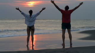 Joyful couple standing on the beach and feels free, steadycam shot, slow motion