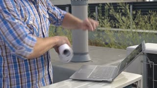 Man checking plan about air condition and compares with information on laptop, s