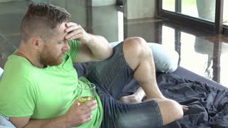 Man drinking alcohol while lying on the bed and looks worried, steadycam shot