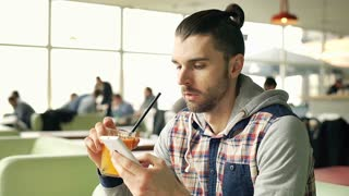 Man drinking orange juice and looks bored while browsing internet on smartphone,