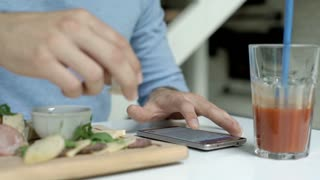 Man eating lunch and reading news on smartphone