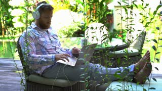 Man finish listening music and using laptop in exotic garden