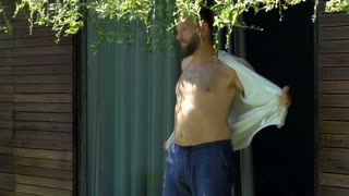 Man goes outside and takes off shirt, steadycam shot, slow motion shot at 240fps