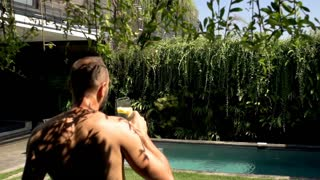 Man going outside to the garden while drinking water, steadycam shot, slow motio