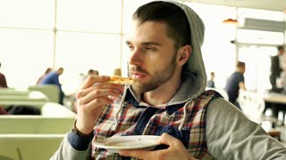 Man in hood looks dissatisfied while eating tasteless pizza, steadycam shot
