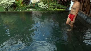 Man jumping to the pool and swimming, slow motion shot at 240fps, steadycam shot