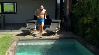 Man jumping to the swimming pool and splashing water, steadycam shot, slow motio