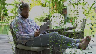 Man listening music in the garden and playing a game on modern notebook