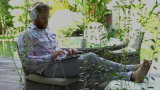 Man listening music in the garden and using modern notebook