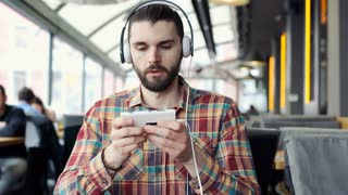 Man look irriated while listening music and texting messages on smartphone