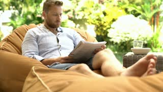 Man looks absorbed while reading magazine on the bean bag chair