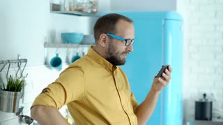 Man looks absorbed while watching interesting video on smartphone in his modern