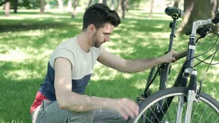 Man looks worried while checking his bicycle in the park, steadycam shot