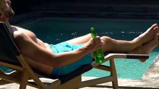 Man lying on sunbed and drinking beer, steadycam shot, slow motion shot at 240fp