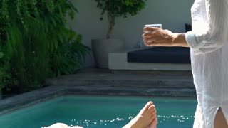 Man lying on sunbed and having a drink, steadycam shot, slow motion shot at 240f