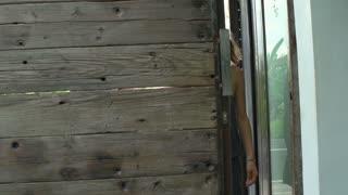 Man opens wooden door and walks in with a girlfriend, steadycam show, slow motio