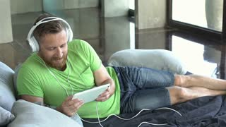 Man relaxing on the bed and listening music on tablet