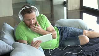 Man relaxing on the bed and watching something on tablet