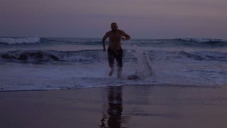 Man running at night in the sea, slow motion shot at 240fps, steadycam shot