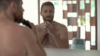 Man shaving his beard in the bathroom and smiling to the camera
